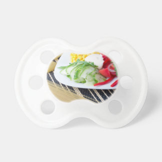 Pieces of fresh raw vegetables on a white plate baby pacifiers