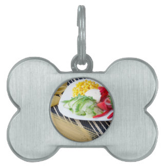 Pieces of fresh raw vegetables on a white plate pet name tag