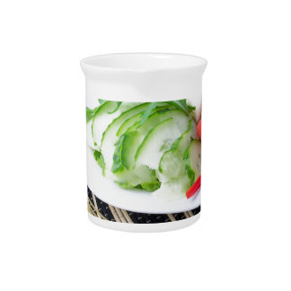 Pieces of fresh raw vegetables on a white plate pitcher