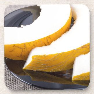 Pieces yellow melon on a black plate beverage coaster