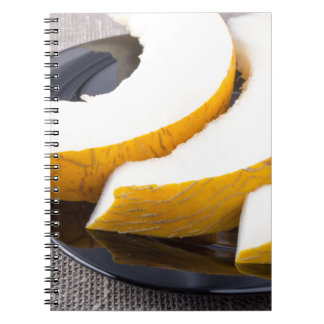 Pieces yellow melon on a black plate note books