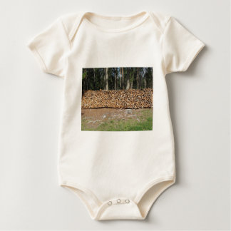 Pile of firewood with forest background baby bodysuit