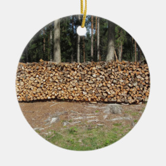 Pile of firewood with forest background ceramic ornament