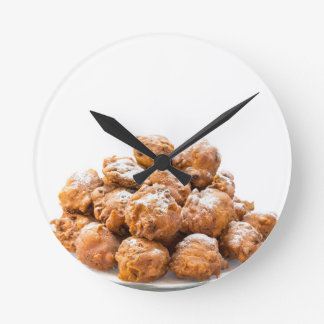 Pile of sugared oliebollen or fried fritters round clock
