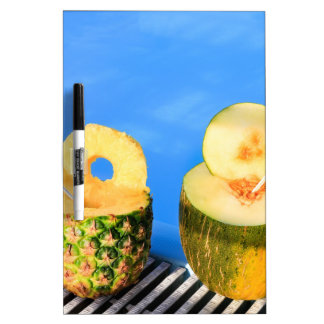 Pineapple and melon fruit with straws at pool dry erase board