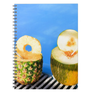 Pineapple and melon fruit with straws at pool note books