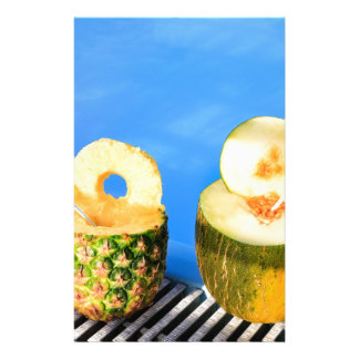 Pineapple and melon fruit with straws at pool stationery