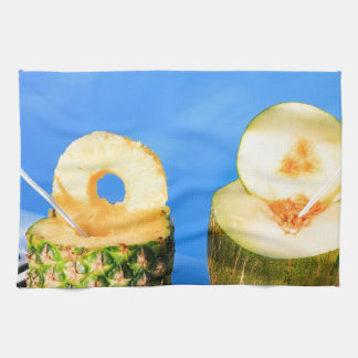 Pineapple and melon fruit with straws at pool tea towel