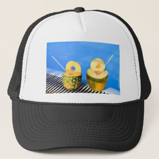 Pineapple and melon fruit with straws at pool trucker hat