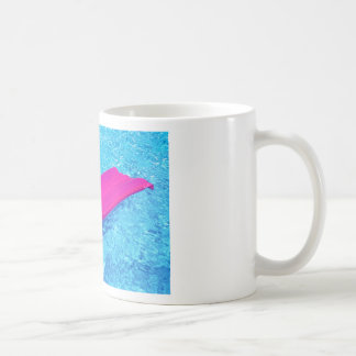 Pink air mattrass with hat in swimming pool coffee mug