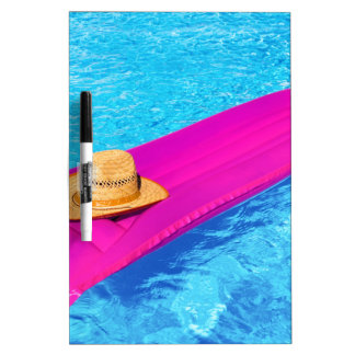 Pink air mattrass with hat in swimming pool dry erase white board
