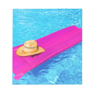 Pink air mattrass with hat in swimming pool notepads