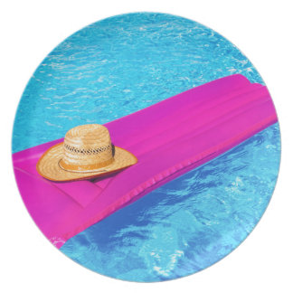 Pink air mattrass with hat in swimming pool plate