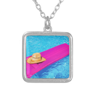 Pink air mattrass with hat in swimming pool silver plated necklace