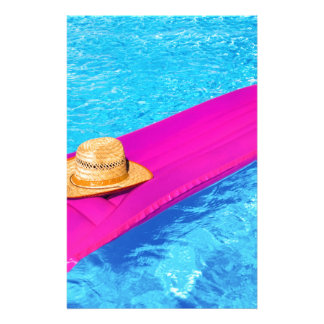 Pink air mattrass with hat in swimming pool stationery