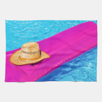 Pink air mattrass with hat in swimming pool tea towel