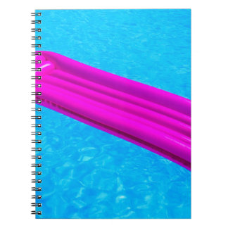 Pink air mattress on water of swimming pool spiral notebook