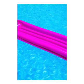 Pink air mattress on water of swimming pool stationery