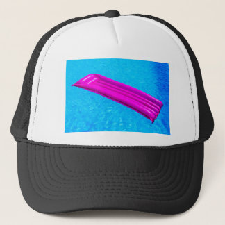 Pink air mattress on water of swimming pool trucker hat