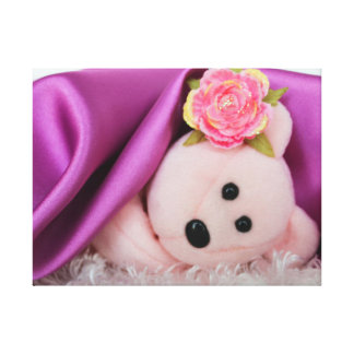 PINK BEAR UNDER A PURPLE SATIN BLANKET STRETCHED CANVAS PRINT