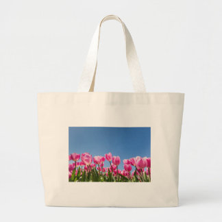 Pink tulips field with blue sky large tote bag