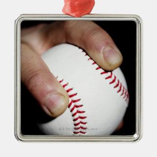 Pitchers hand gripping a baseball metal ornament