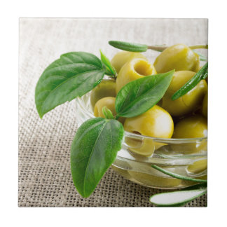 Pitted olives with green leaves and rosemary small square tile