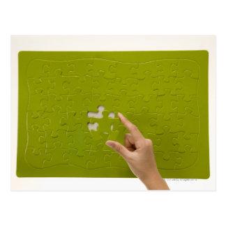 Placing a puzzle piece postcard
