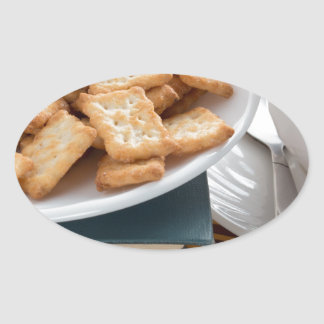 Plate with crackers and cup of tea oval sticker