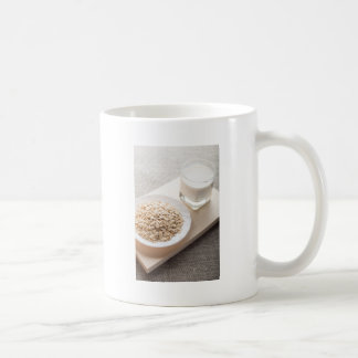 Plate with dry cereal and a glass of milk coffee mug