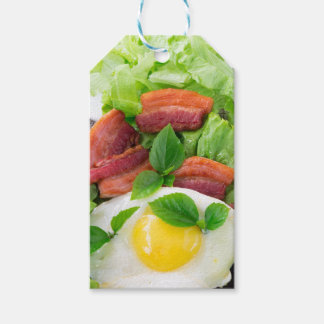 Plate with egg yolk, fried bacon and herbs gift tags