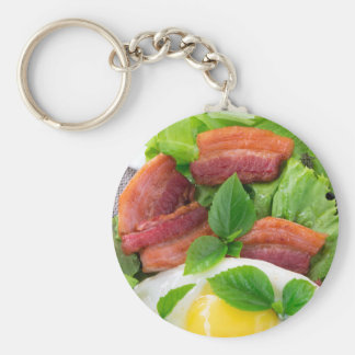 Plate with egg yolk, fried bacon and herbs key ring