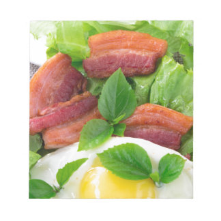 Plate with egg yolk, fried bacon and herbs notepad