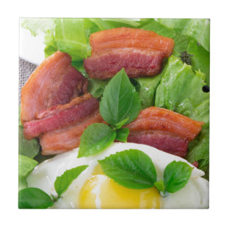 Plate with egg yolk, fried bacon and herbs tile