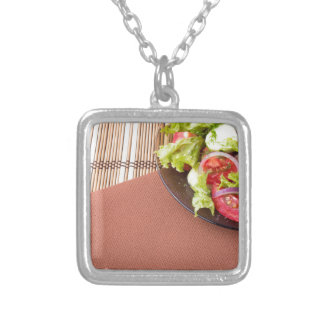 Plate with fresh salad of raw tomatoes and lettuce silver plated necklace