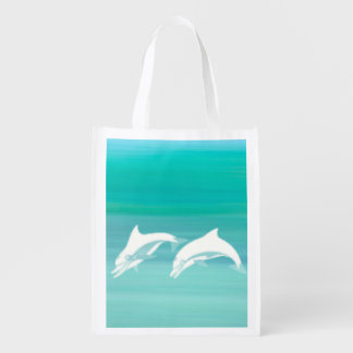 Playful dolphins in aquamarine ocean reusable grocery bag