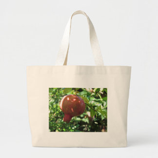 Pomegranate hanging on tree large tote bag