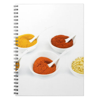 Porcelain bowls and spoons with various spices spiral notebook