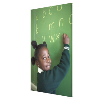 Portrait of smiling schoolgirl writing on the stretched canvas prints