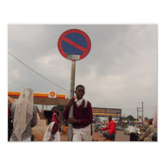 Portrait of Ugandan schoolboy at traffic sign