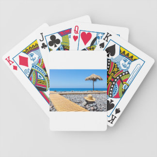 Portuguese stony beach with path sea hat parasols bicycle playing cards