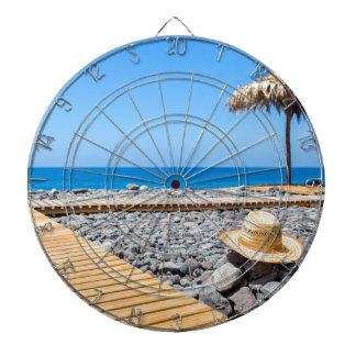 Portuguese stony beach with path sea hat parasols dartboard with darts