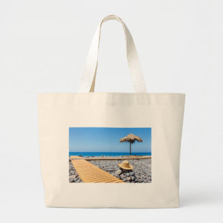 Portuguese stony beach with path sea hat parasols large tote bag