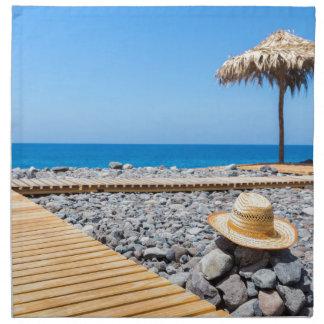 Portuguese stony beach with path sea hat parasols napkin