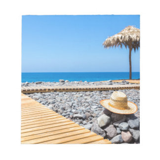 Portuguese stony beach with path sea hat parasols notepad