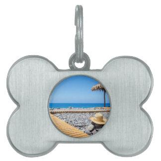 Portuguese stony beach with path sea hat parasols pet ID tag