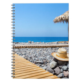 Portuguese stony beach with path sea hat parasols spiral notebook