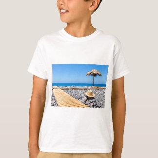 Portuguese stony beach with path sea hat parasols T-Shirt