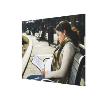 Pregnant Middle Eastern woman reading on park Gallery Wrap Canvas