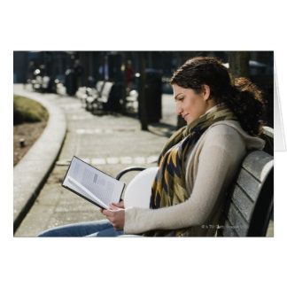 Pregnant Middle Eastern woman reading on park Card